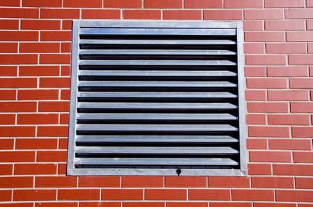 metal grate: metal grate on new brick wall Stock Photo