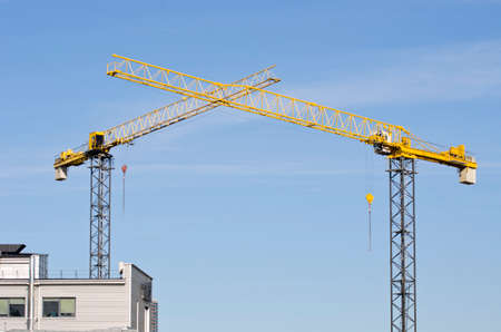 yeloow: two building crane construction on sky background