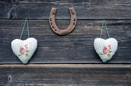 textile cloth hearts on old wooden wall and rusty horseshoe