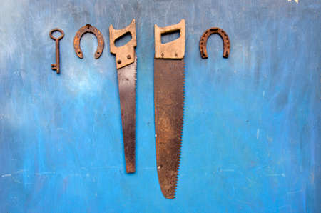 antique garden and farm tools on old blue wooden wall. Rusty metal keay, horseshoe and