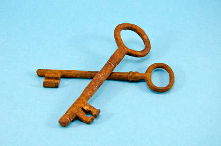 two antique rusty metal key on blue background