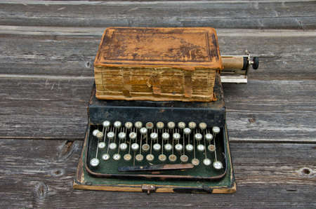 antique typewriter with  old used book Bible on wooden gray background photo
