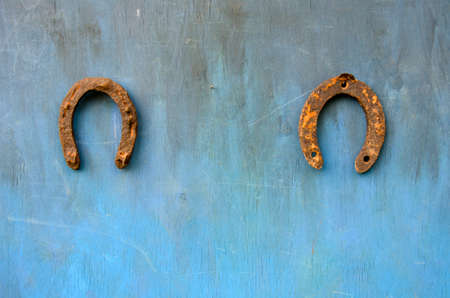 two ancient rusty horseshoe luck symbol on blue wooden wall photo