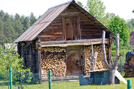 badhuis: old wooden bathhouse with firewood in village