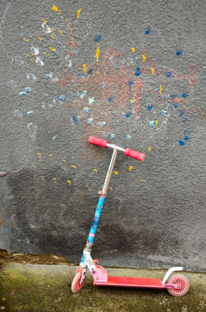 used child  kick scooter near colorful house wall