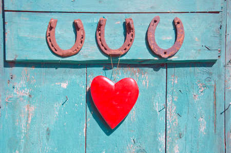 three old rusty horseshoe luck symbol and red heart on green wooden farm door photo