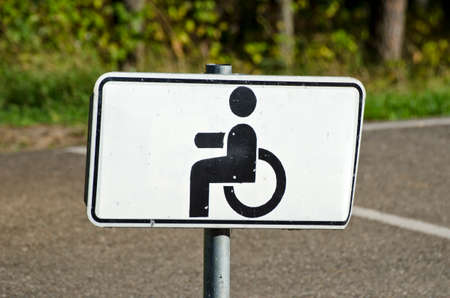 cautionary: Wheelchair Handicap Sign in resort park forest road Stock Photo