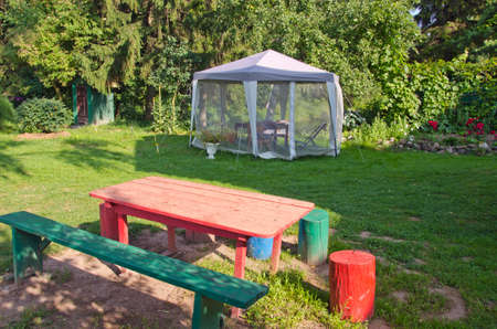 mosquito protection tent in summer garden and handmade furniture photo