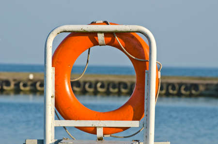life buoy: orange life buoy ring life belt in sea port