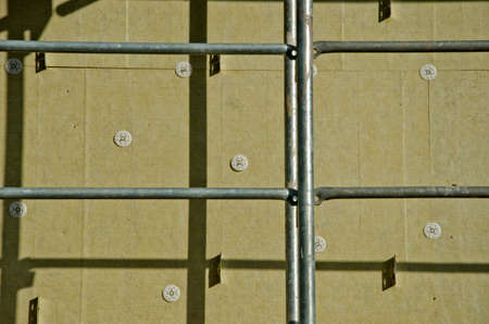 rock wool: urban house wall with insulation material rock wool and scaffold