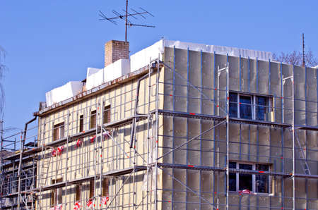 old urban house renovation thermal insulation works and scaffolding