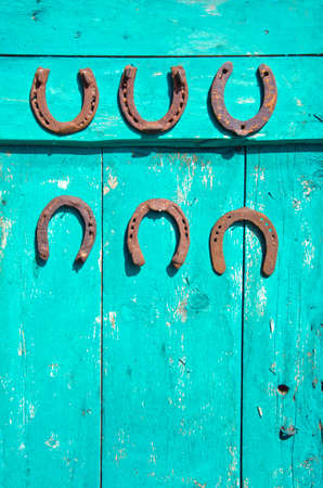 six antique rusty horseshoe on old green wooden farm barn door