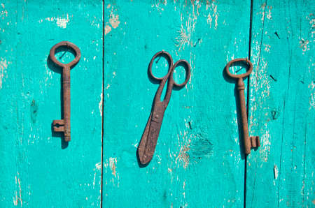 two antique metal key and rusty scissors on wooden green wall photo