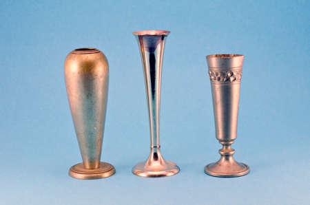 antique vase: three antique metal silver goblet cup vase on blue background