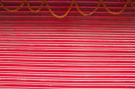 red painted corrugated metal door and flowers garland background photo