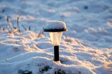 garden lamp: snowy solar garden lamp in winter time