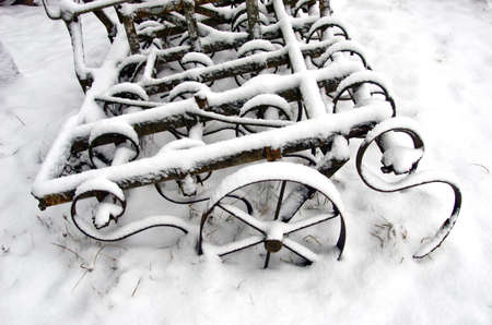 agriculture equipment rake tool on snow in farm photo