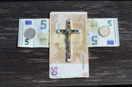sacrosanct: euro money cross and metal crucifixion with Jesus concept Stock Photo
