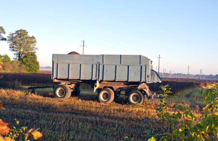 tractor trailer: agriculture tractor trailer on farm field in autumn morning Stock Photo