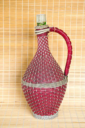 osier: vintage wicker braided wine bottle on table