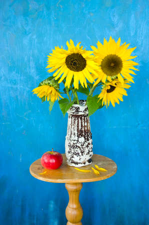 antique vase: antique vase with beautiful sunflowers and red apple on table
