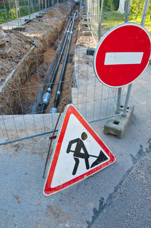 energetics: new heating system pipes in trench and road signs on street