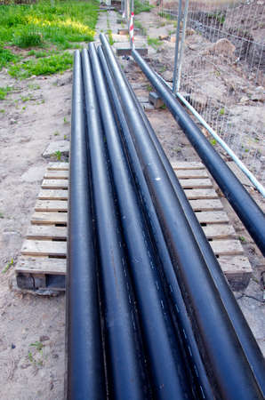 trench: new industrial plastic heating pipes tube stack near trench in city Stock Photo