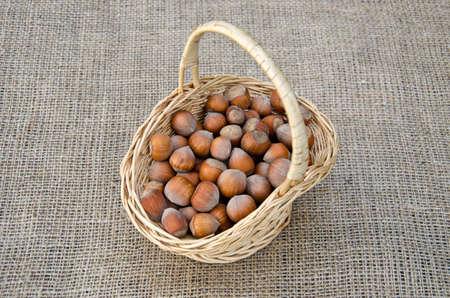 wicket: Hazel nuts in wicket basket on linen - healthy food