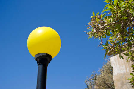 lampost: Vividly yellow lampost in the daylight