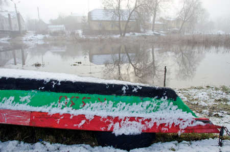 upturned: Upturned old wooden boat by river in winter time