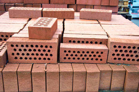 holed: Stack of red clay bricks with holes in market