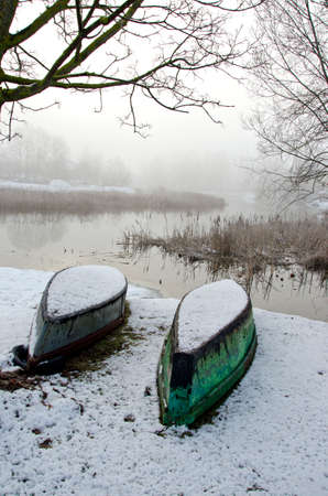 upturned: One green and one blue upturned boat in winter by the lake