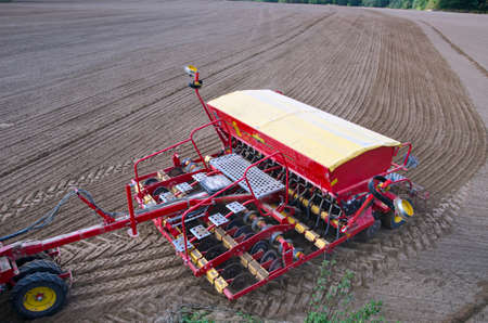 plough machine: Tractor sowing crop wheat seeds in freshly plowed farm field