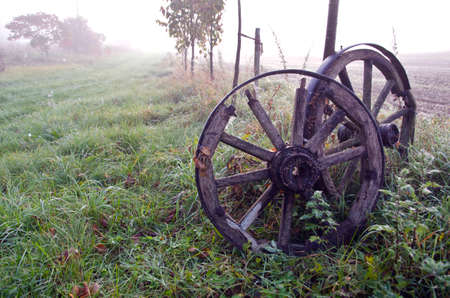 horse and carriage: Sunrise on foggy autumnal landscape with two antique horse carriage wooden wheels Stock Photo