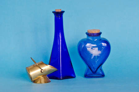 corked: Two decorative blue glass bottles with decorative brass object on blue background