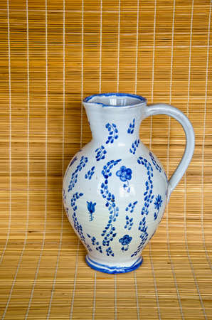 voluminous: White and blue jug on bamboo material background