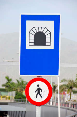 highway tunnels: Road sign of a tunnel and a sign forbidding to walk in tropical urban area