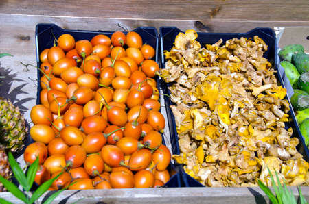 tamarillo: Tamarillo and chanterelle in plastic boxes on a stall outdoors for sale on sunny day