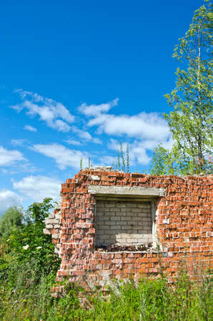 desolate: Crumbling desolate brick house in the overgrown meadow on sunny day with cloudy blue sky
