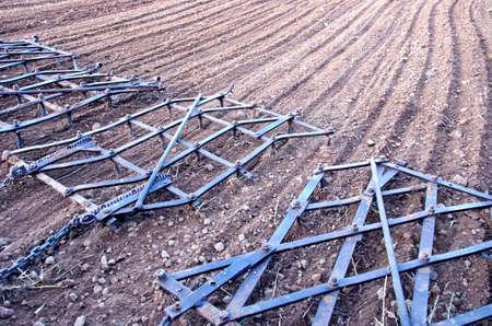 agriculture machinery: Agriculture machinery metal harrow rake on plowed farm field Stock Photo