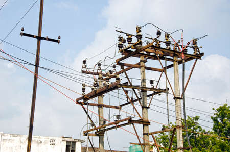 isolators: rusted electricity poles with many wires in urban area, India