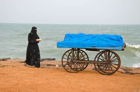 tamilnadu: India Puducherry trolley with muslim woman walking by on the beach by the ocean