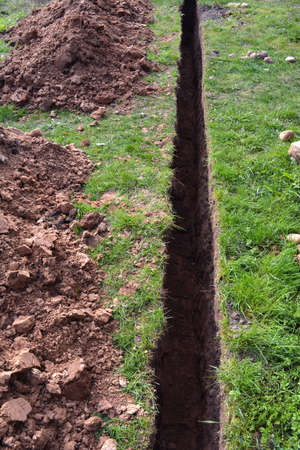 trench: very narrow trench in summer farm yard through grass  for water pipe
