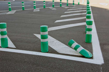 White and green  delineator posts in car parking lot