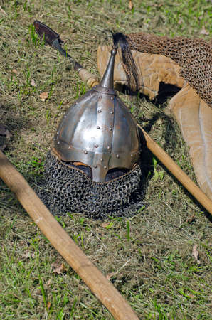 crusaders: Knight armor headpiece and weapons on grass at medieval festival