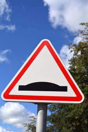 triangle shaped: Triangle shaped road sign with red and white and black bump
