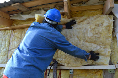rock wool: Builder  insulating wooden house with mineral  rock wool
