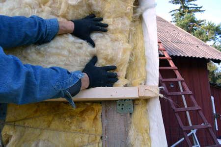 rockwool: worker hands on house wall insulatiom material rockwool