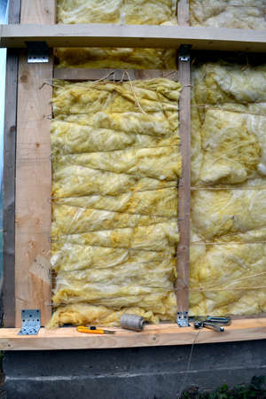 house wall with insulation material rockwool fragment and tools Stock Photo