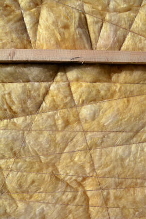 glasswool: home insulation material rock-wool on wall abstract background